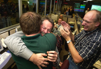 Entry, descent and landing manager, Rob Manning (facing camera), hugs Richard Cook, the current Mars Exploration Rover project manager after Opportunity's successful landing at Meridiani Planum, Mars.