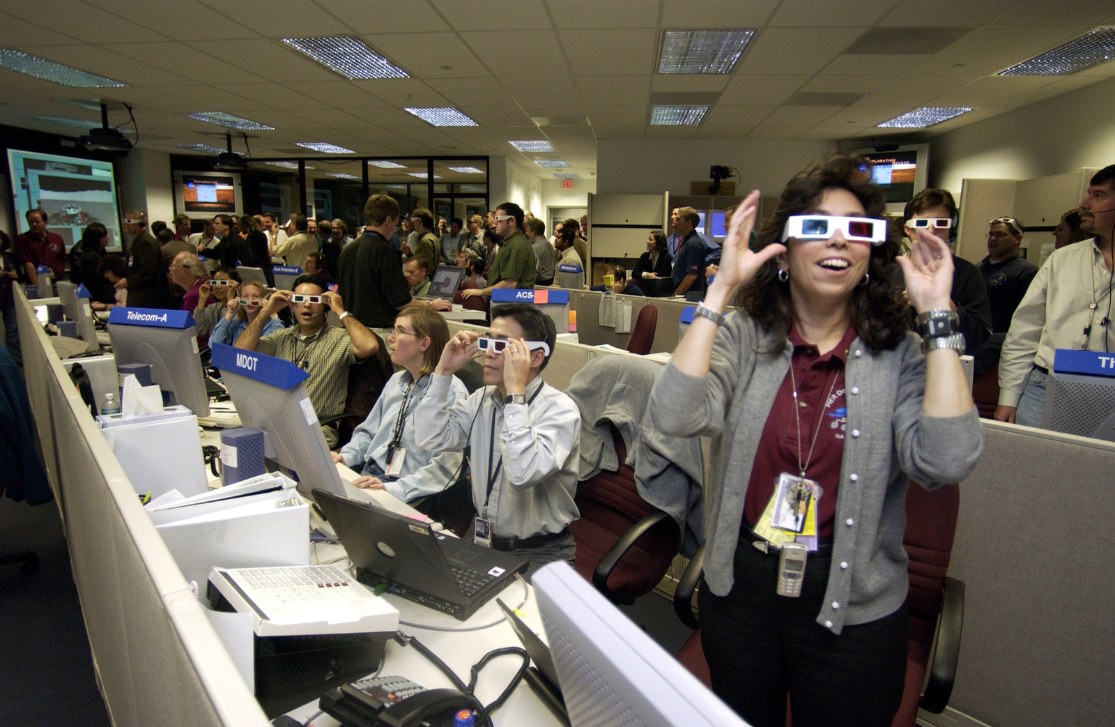 A crowd of excited men and women who work on the Mars Exploration Rover mission are wearing white paper 3-D glasses with red and blue lenses to view some of the Spirit rover's first three-dimensional images.  Some are seated behind console work stations, while others are standing, trying to get the best view. 	Team members viewing some of Spirit's first 3-D images