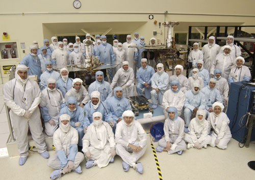 A team of about 50 men and women in white and blue cleanroom smocks and bonnets  stand and sit around their creations: Spirit and Opportunity.  The twin rovers of the Mars Exploration Rover mission are about the size of golf carts.  The significantly smaller, microwave-sized Sojourner rover from the 1997 Pathfinder mission sits in the middle.