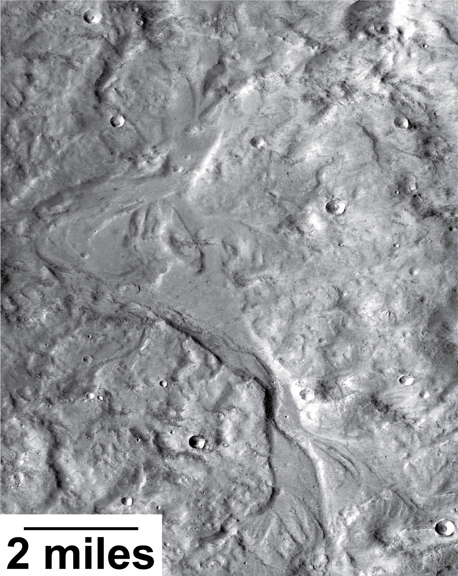 Streamlined forms in this Martian valley resulted from the outflow of a lake hundreds of millions years more recently than an era of Martian lakes previously confirmed. This image from the Context Camera on NASA's Mars Reconnaissance Orbiter covers an area in Arabia Terra about 8 miles wide.