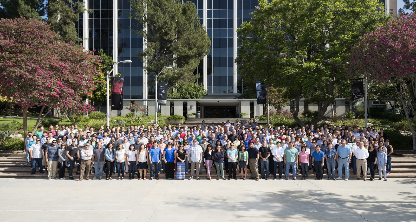 About 100 team members stand in a group photo in front of the steps of a large administration building.