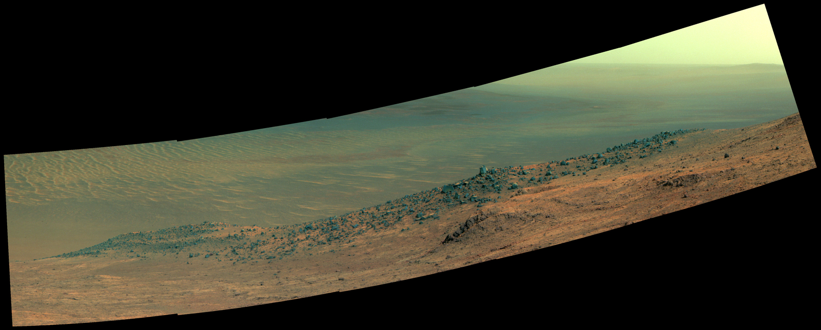 "This scene from NASA's Mars rover Opportunity shows ""Wharton Ridge,"" on the western rim of Endeavour Crater. The ridge's name honors the memory of astrobiologist Robert A. Wharton (1951-2012). The scene is presented in enhanced color to make differences in surface materials more easily visible."