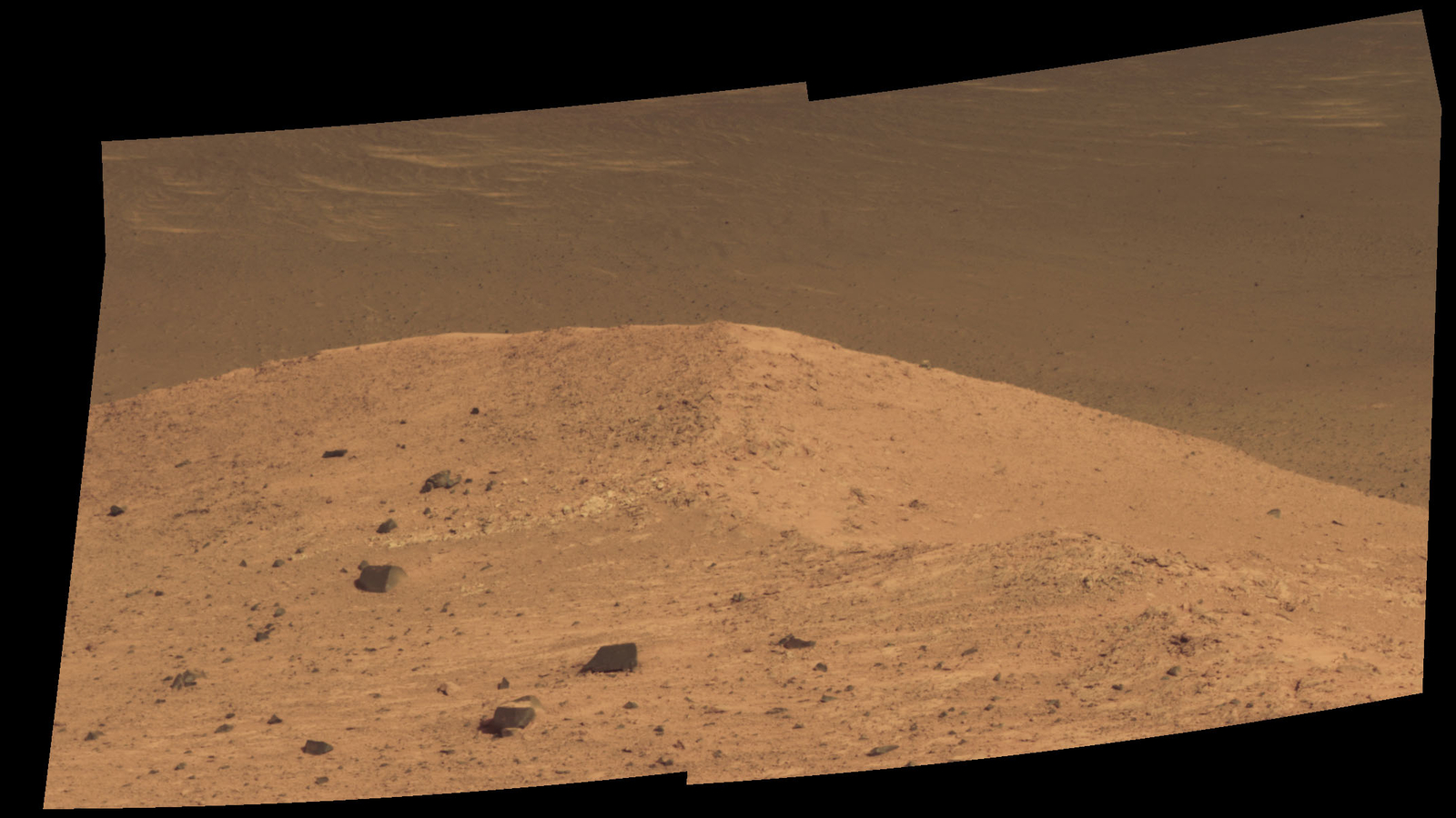 "This Sept. 21, 2016, scene from the panoramic camera (Pancam) on NASA's Mars Exploration Rover Opportunity shows ""Spirit Mound"" overlooking the floor of Endeavour Crater. The mound stands near the eastern end of ""Bitterroot Valley"" on the western rim of the crater, and this view faces eastward."