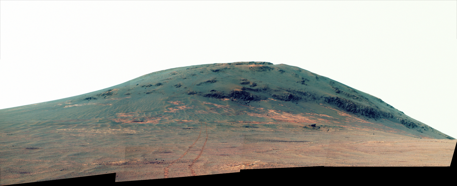 "Wheel tracks from NASA's Mars rover Opportunity descending and departing the ""Cape Tribulation"" segment of Endeavour Crater's rim are visible in this April 21, 2017, view from the rover's Pancam. This version is presented in enhanced color to make differences in surface materials more visible."