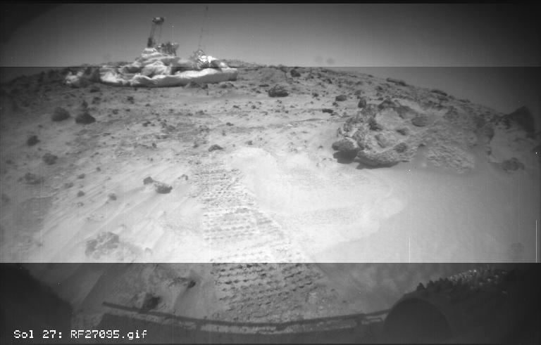 This image from NASA's Sojourner rover's right front camera was taken on Sol 27. The Pathfinder lander is seen at middle left. The large rock at right, nicknamed 'Squash,' exhibits a diversity of textures. Sol 1 began on July 4, 1997.