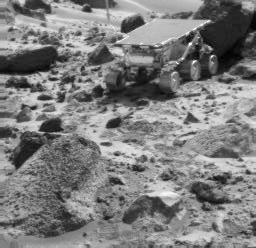 NASA's Sojourner rover is seen next to the rock 'Shark,' in this image taken by the Imager for Mars Pathfinder (IMP) near the end of daytime operations on Sol 52. The rover's APXS is deployed against the rock. The rock 'Wedge' is in the foreground.