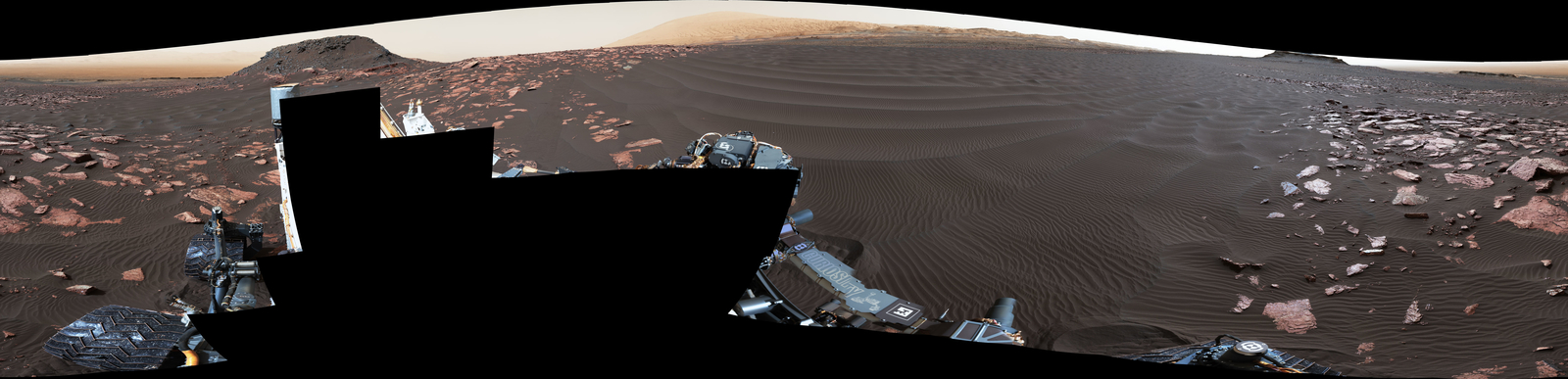 "A rippled linear dune of dark Martian sand, ""Nathan Bridges Dune,"" dominates this full-circle panorama from the Mastcam of NASA's Curiosity Mars rover. This dune was one research stop of the mission's campaign to investigate active Martian dunes. Nathan Bridges (1966-2017) helped lead that campaign"