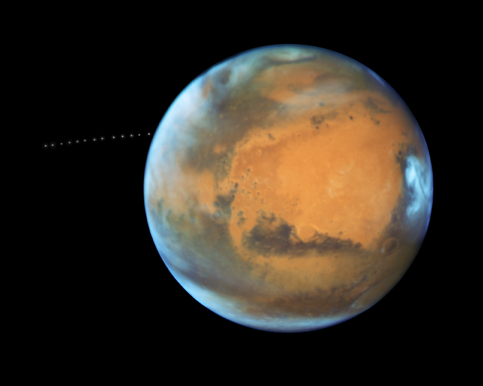 While photographing Mars, NASA's Hubble Space Telescope captured a cameo appearance of the tiny moon Phobos on its trek around the Red Planet.