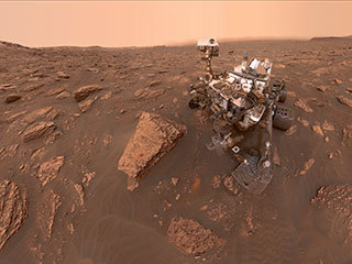 "A self-portrait by NASA's Curiosity rover taken on Sol 2082 (June 15, 2018). A Martian dust storm has reduced sunlight and visibility at the rover's location in Gale Crater. A drill hole can be seen in the rock to the left of the rover at a target site called ""Duluth."""