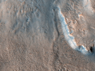 This image, acquired by NASA's Mars Reconnaissance Orbiter on April 29, 2018, shows an impact crater, approximately 23 kilometers across, that is home to fan-shaped deposits that extend from the rim and sit on the interior crater floor.