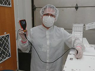 JPL mechanical technician Eddie Castro uses a paint meter to measure the paint thickness on the Mars 2020 rover chassis.