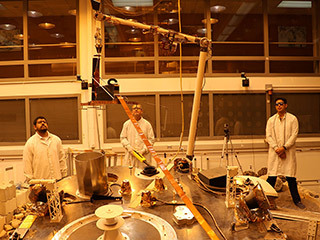 An engineering version of the robotic arm on NASA's InSight mission lifts the engineering version of the Heat Flow and Physical Properties Probe (HP3) at NASA's Jet Propulsion Laboratory.