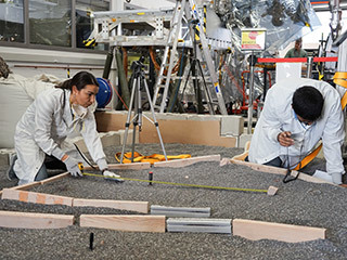 "Engineers Marleen Sundgaard (left) and Pranay Mishra measure their test lander's ""workspace"" -- the terrain where scientists want to set InSight's instruments -- at NASA's Jet Propulsion Laboratory in Pasadena, California."