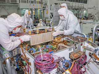Technicians at JPL integrate the rover motor controller assembly (RMCA) into the Mars 2020 rover's body