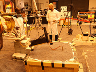 Engineers in a Mars-like test area at NASA's Jet Propulsion Laboratory try possible strategies to aid the Heat Flow and Physical Properties Package (HP3) on NASA's InSight lander, using engineering models of the lander, robotic arm and instrument.