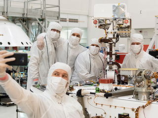 ​​Members of NASA's Mars 2020 project take a moment after attaching the remote sensing mast to the Mars 2020 rover.