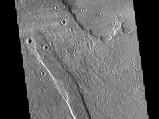 This image from NASAs Mars Odyssey shows lava flows from Alba Mons, and a tectonic graben called Cyane Fossae.