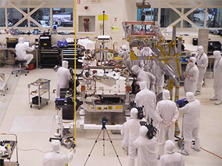 A team of engineers at NASA's Jet Propulsion Laboratory in Pasadena, California, install the legs and wheels — otherwise known as the mobility suspension — on the Mars 2020 rover.