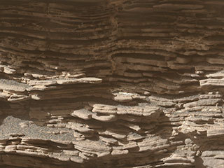 "This mosaic of images shows layers of sediment on a boulder-sized rock called ""Strathdon,"" as seen by the Mars Hand Lens Imager (MAHLI) camera carried by NASA's Curiosity rover. The images were taken on July 10, 2019, the 2,462nd Martian day, or sol, of the mission."