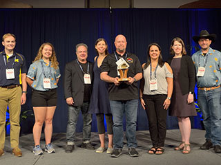 JPL engineer Glen Elliott (center) holds the 2019 Small Satellite Mission of the Year Award alongside others who supported the MarCO mission. Left to right: Matthew Szczerba, Kate Parkinson, Ben Malphrus, Kerri Cahoy, Glen Elliott, Chloe Hart, Emily Clements and John Belardo.