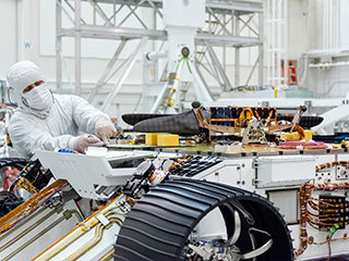 Engineers attached NASA's Mars Helicopter to the belly of the Mars 2020 rover on Aug. 27, 2019, at the Jet Propulsion Laboratory in Pasadena, California.