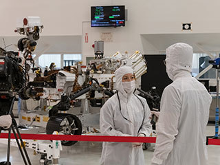 A member of the media interviews mission team member Jessica Samuels inside JPL's High Bay 1 clean room on Dec. 27, 2019, during Mars 2020 media day.