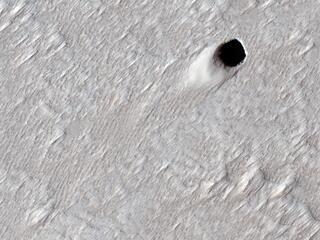 This image acquired on August 16, 2020 by NASAs Mars Reconnaissance Orbiter, shows the ceiling of a lava tube has collapsed in one spot and made this pit crater.