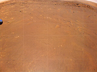 "NASA's Ingenuity Mars Helicopter took this color image during its fourth flight on April 30, 2021. ""Airfield B,"" it's new landing site, can be seen below; it will seek to set down there on its fifth flight attempt."