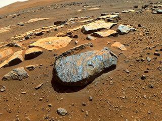 """This is a colored image taken by the Perseverance rover of the Martian rock nicknamed """"Rochette"""" after it abraded a circular patch known as """"Bellegarde."""" The patch is about 0.39 inches (10 millimeters) deep and about 2 inches (5 centimeters) in diameter. The main image was taken by one of the rover's Hazard Avoidance Cameras. A secondary image in which part of the rover deck is visible shows the abrasion patch from the point of view of a Navigation Camera on Perseverance's mast."""