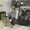 In this video clip, the camera swerves around the room where testing is underway for Curiosity's robotic arm. The camera zooms in on the robotic arm as the arm moves up from the stowed position and then rotates a set of tools at the end of the arm. A JPL engineer is crouched down behind the arm in the background and gives a thumbs-up once the tools stop rotating.